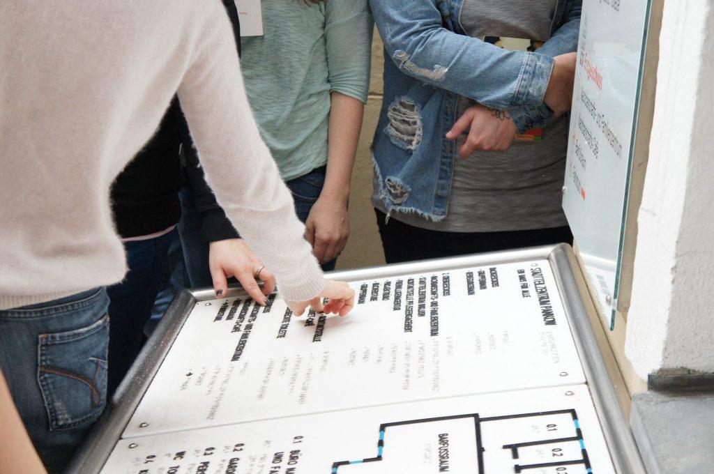 Mehrere Menschen stehen um einen taktilen Grundrissplan. Zwei ertasten mit ihren Fingern die erhabenen Buchstaben.