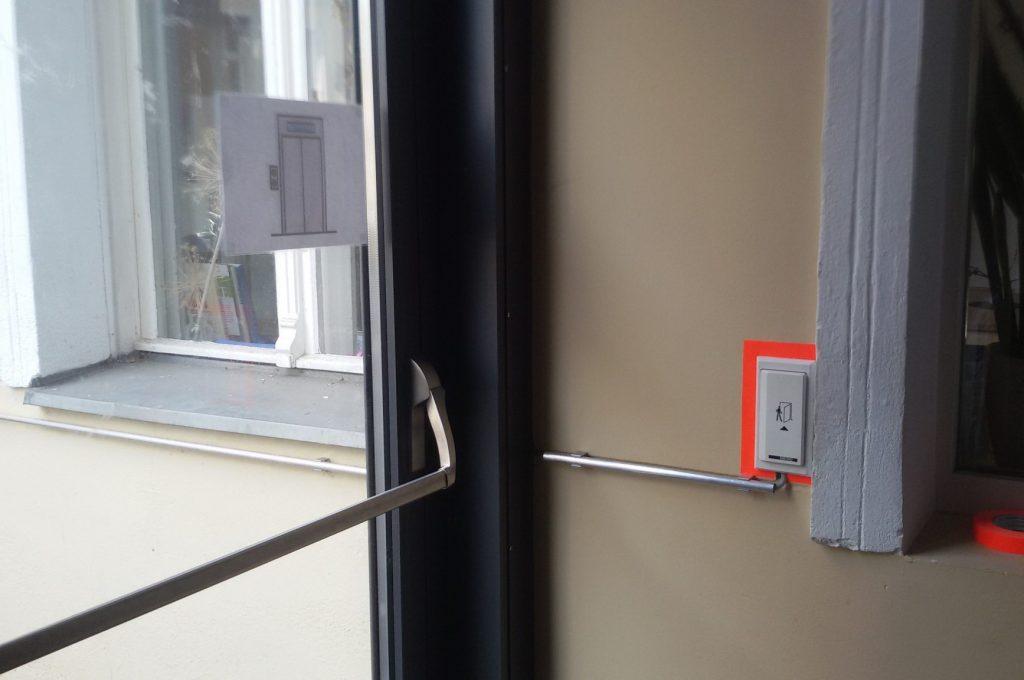 Eingangstür von innen. Innen und außen automatische Türöffner mit einem neonfarbenen Klebeband hervorgehoben.
